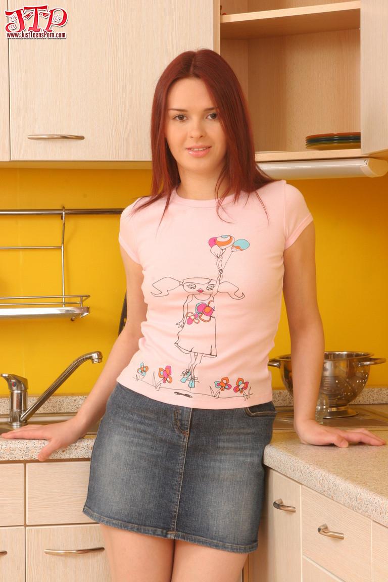 Рыжеволосая девушка с небольшими грудями показывает пилотку на кухне