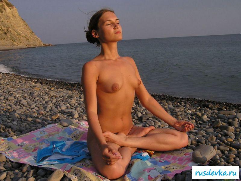 Обнаженная чика лежит под солнцем на гальке с великолепной пиздой