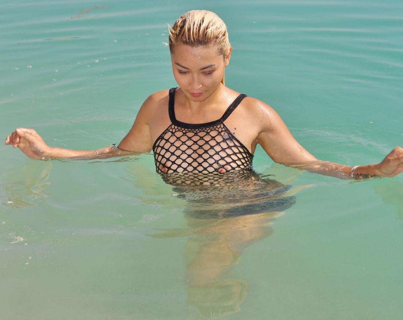 Блондинка с татухой крыльев на спине, изгибается в всевозможных позах у моря