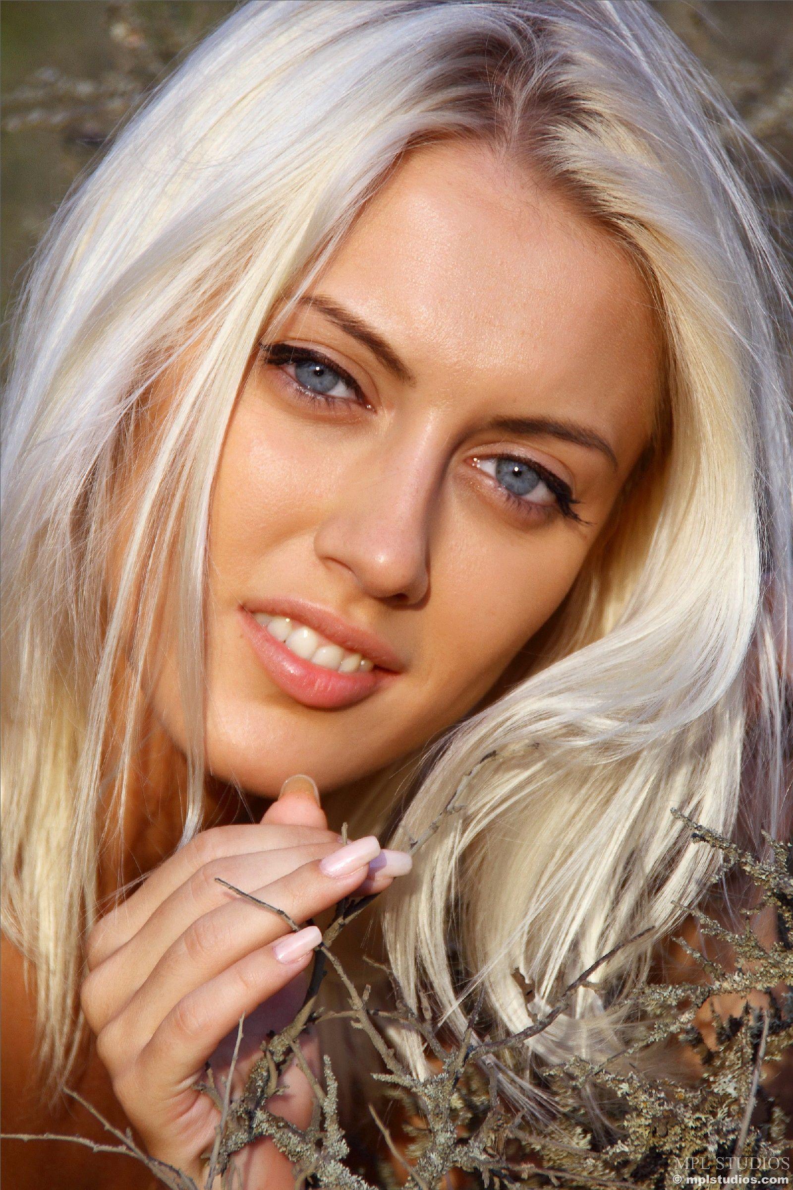 Блондинка в лесу позирует перед фотоапаратом в сексуальных позах