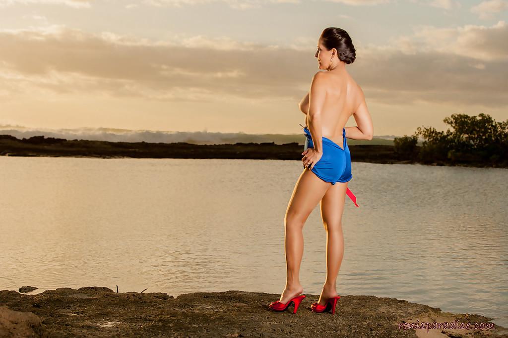 Возбуждённая модель хвастается без одежды на закате около реки