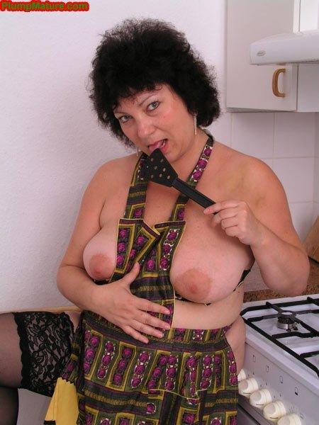 Взрослая толстая домохозяйка на кухне